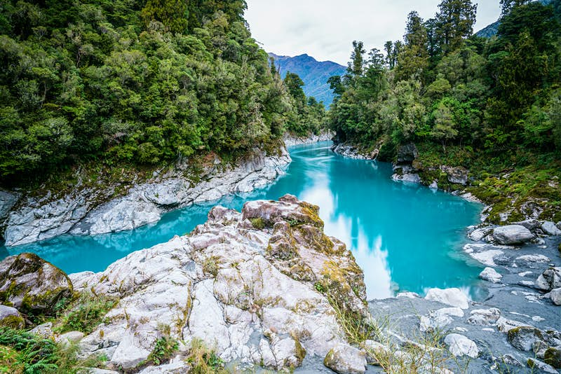 Bright blue water inside a tree-lined gorge.