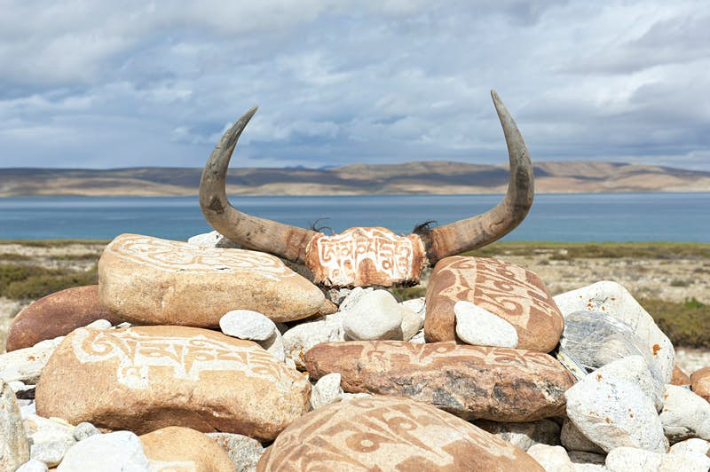 Yak horns and red stones covered in white Tibetan script are in a pile with the lake in the background.