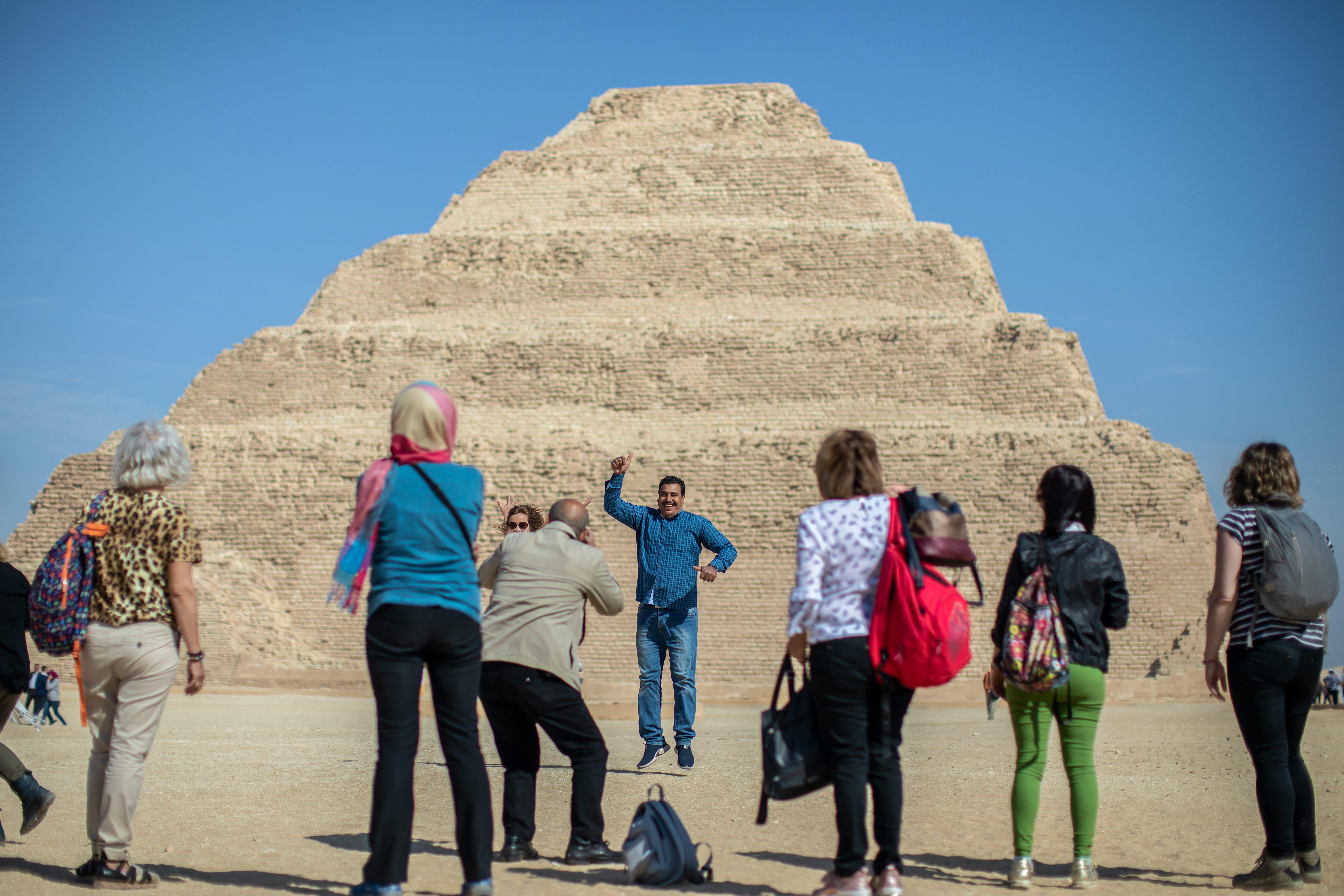 Los turistas toman fotografías de recuerdo frente a la Pirámide de Djoser en Saqqara, a las afueras de El Cairo.