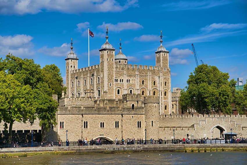 "A fortress-like building with four towers by the side of a river. A sign is painted on a wall at the edge of the water. It says: ""Entry to the Traitors' Gate""."