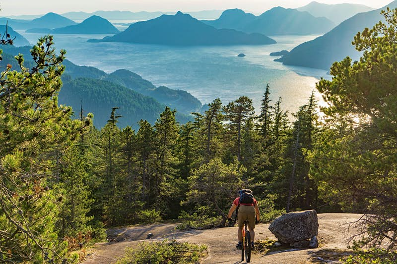 A mountain biker descends down a massive granite outcrop towards the forest below; in the distance far below is a spellbinding scene of forested islands jutting out of the ocean.