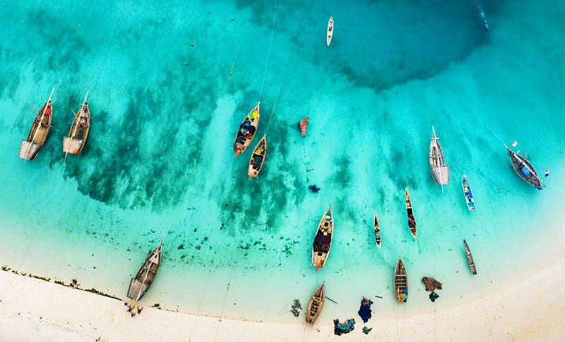 A drone shot shows the crystal blue waters and boats at a beach in Zanzibar.