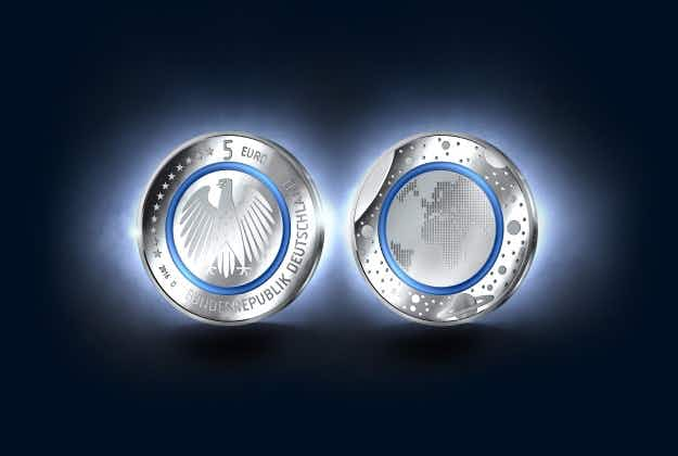 New five Euro coin features transparent blue ring and is designed to look like the Earth