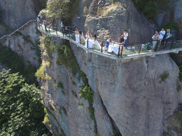 See people enjoy a meal on a glass-bottomed bridge in China