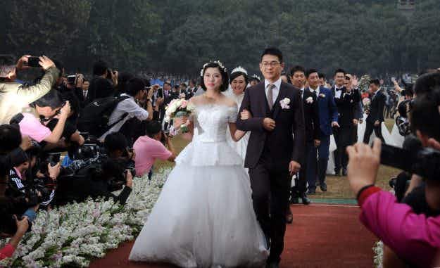 Hundreds of couples get married in group ceremony to celebrate Chinese university
