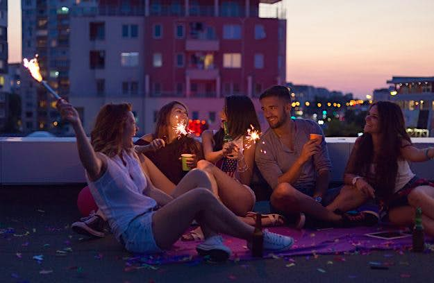 Travel News - Happy friends enjoying a rooftop party