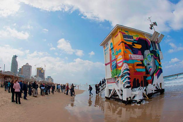 lifeguard tower hotel People look at a lifeguard tower converted into a pop-up hotel in the Israeli coastal city of Tel Aviv on March 14, 2017. The luxury ocean-front hotel suite was designed by Rafael Edger, with interiors by Aline Langlieb and exterior graffiti by artist Edgar Rafael.