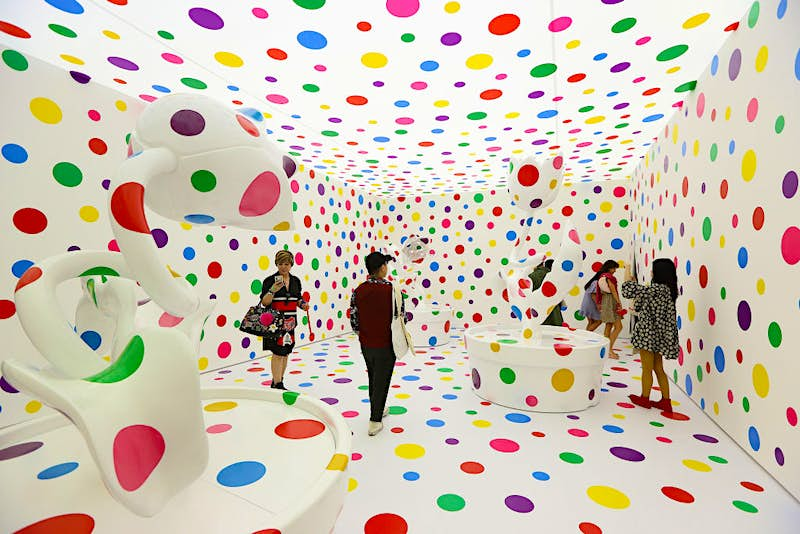 Visitors stand inside Japanese artist, Yayoi Kusama's metal, fibreglass, urethane and paint, stickers installation titled 'With All My Love for Tulips, I Pray Forever 2013'. Image by: Getty Images