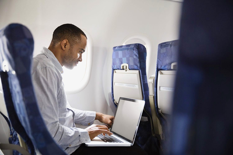 Travel News - Man using laptop in airplane