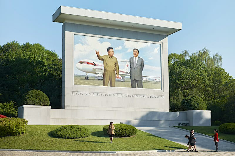 A mural of North Korea's former leaders Kim Jong-il and Kim Il Sung with an aircraft.