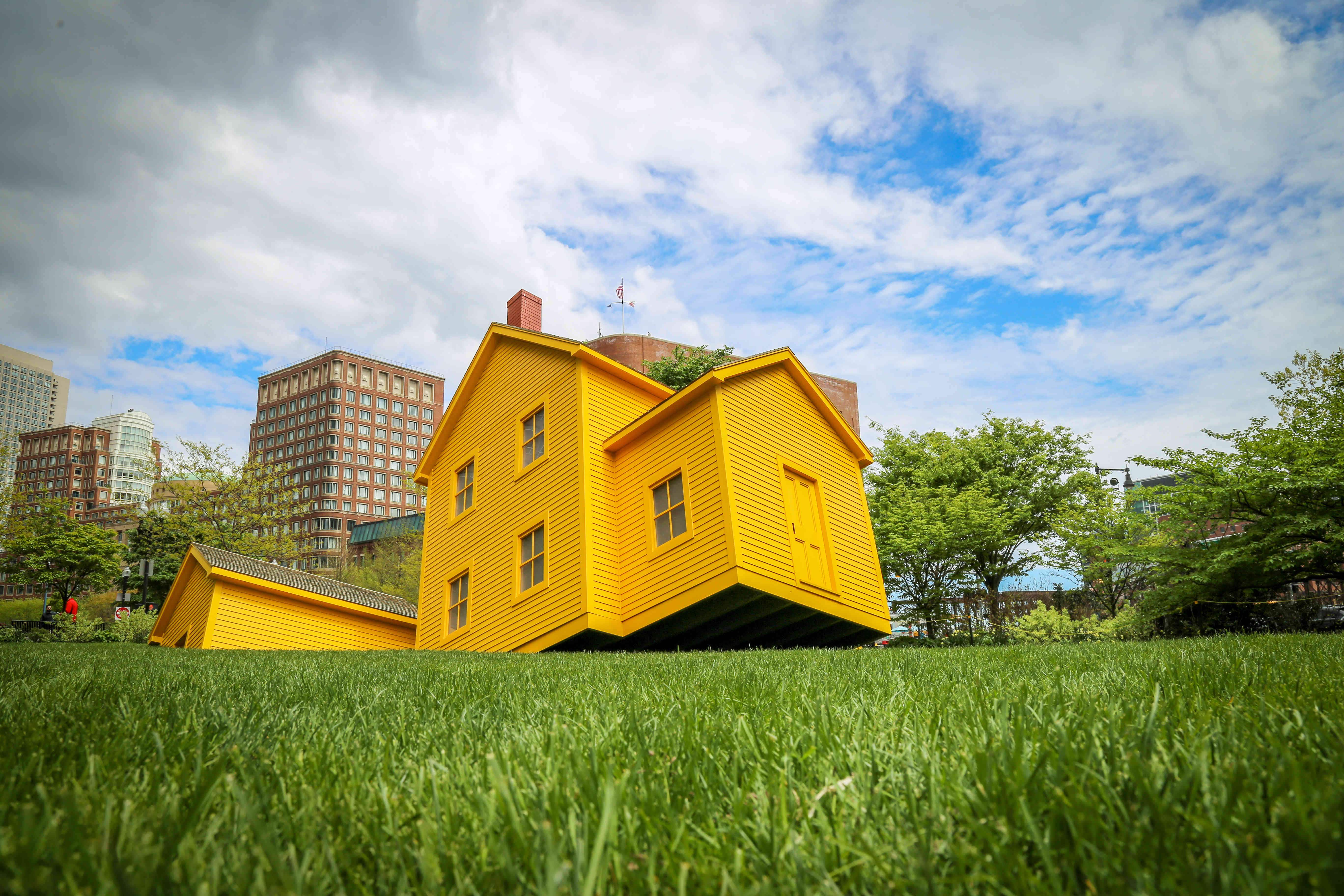 A yellow Quaker-style house is sinking into the ground in downtown Boston