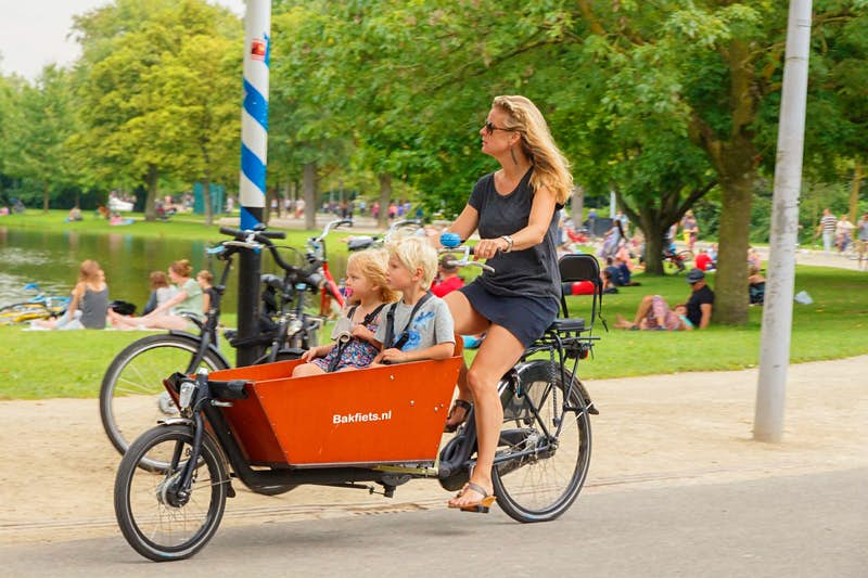A woman cycling a cargo bike with children in Amsterdam.