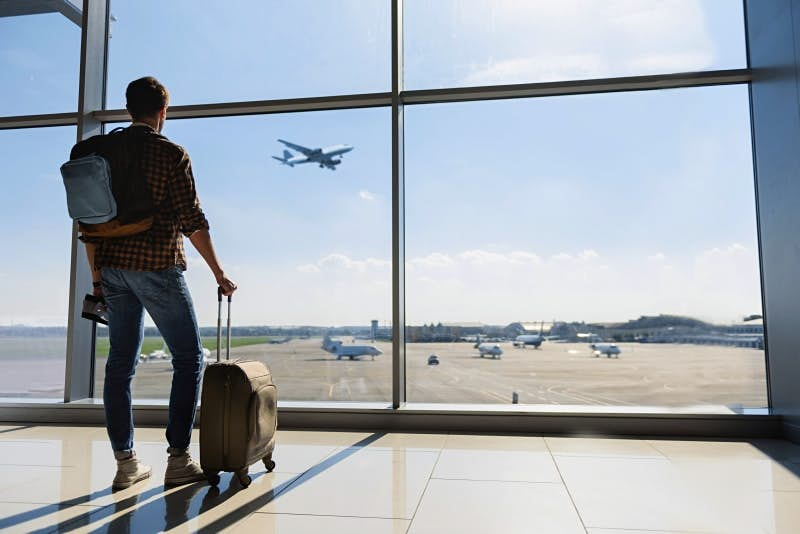 Travel News - Male tourist looking at flight
