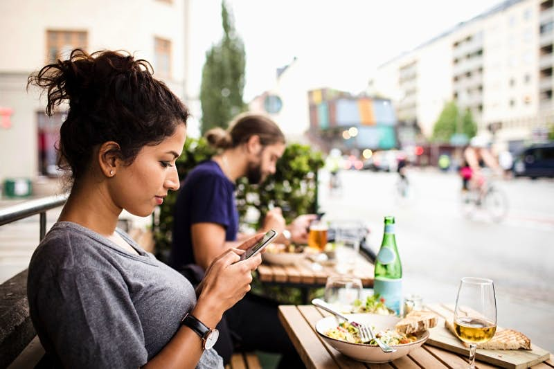 Travel News - Side view of woman text messaging while having food at sidewalk cafe in city