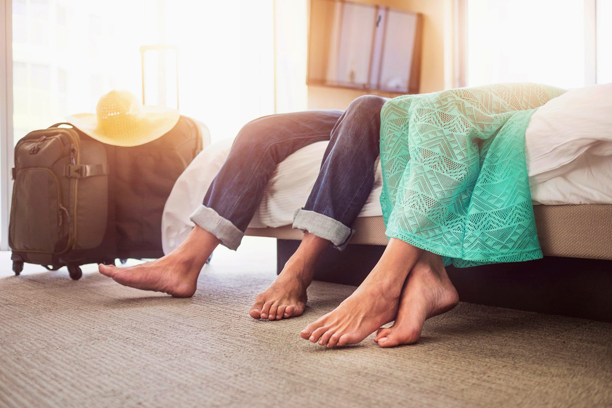 Travel News - Legs of couple laying on bed in hotel room