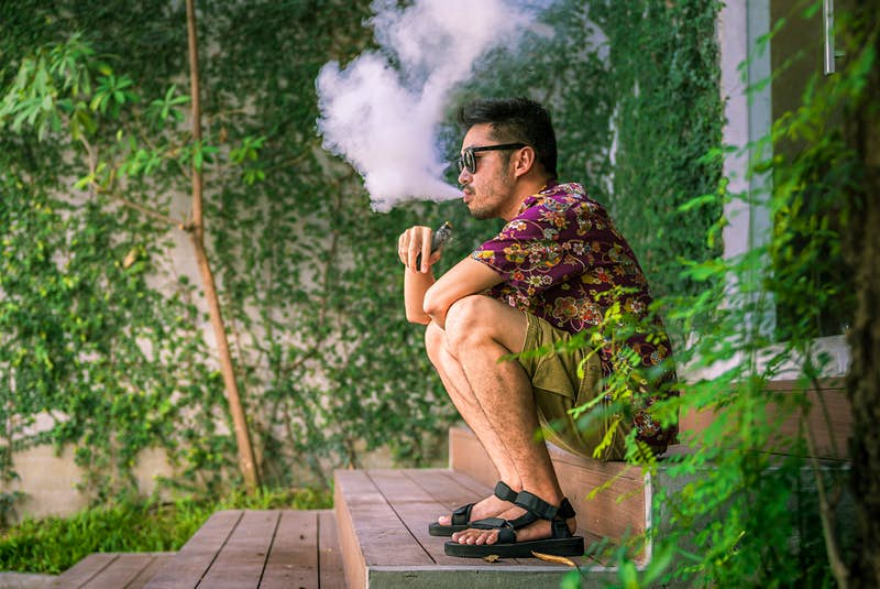 Man smoking an electric cigarette sitting on a step