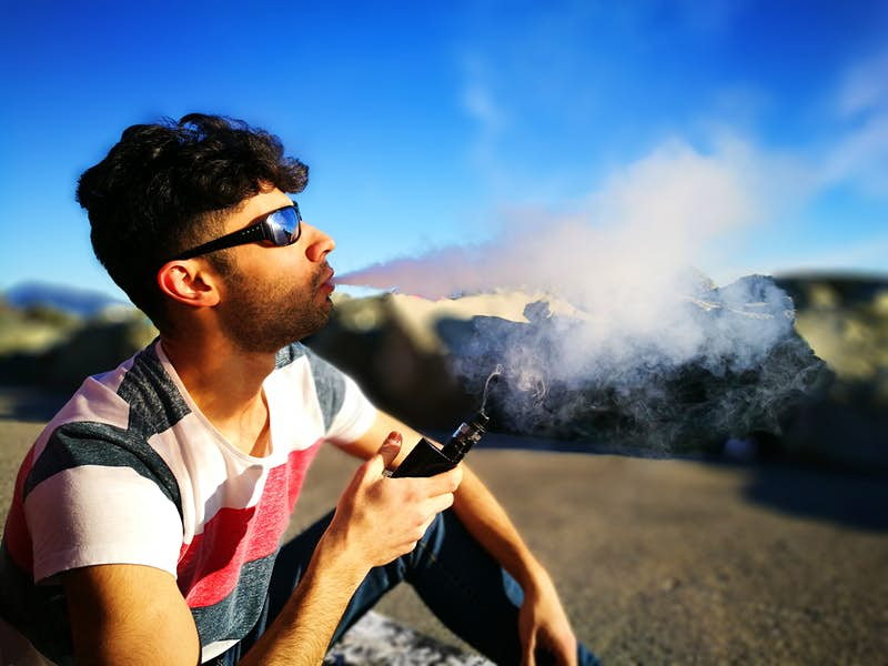Young Man Smoking Electronic Cigarette While Sitting On Field Against Sky