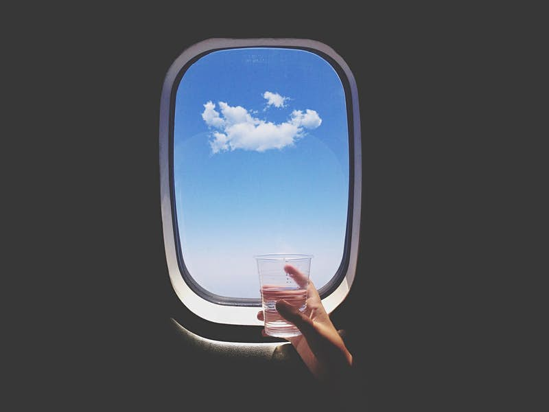 Travel News - Close-Up Of Hand Holding Glass Of Water In Front Of Airplane Window