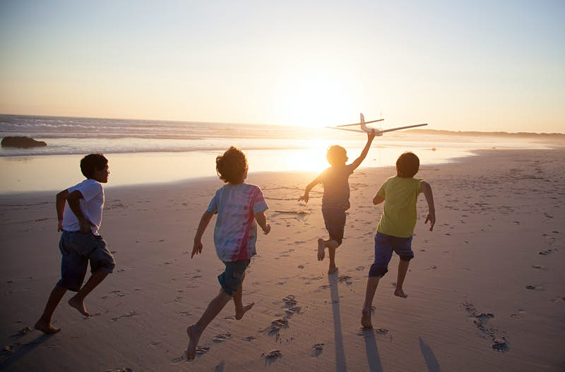 Travel News - Boys running along beach with a toy plane