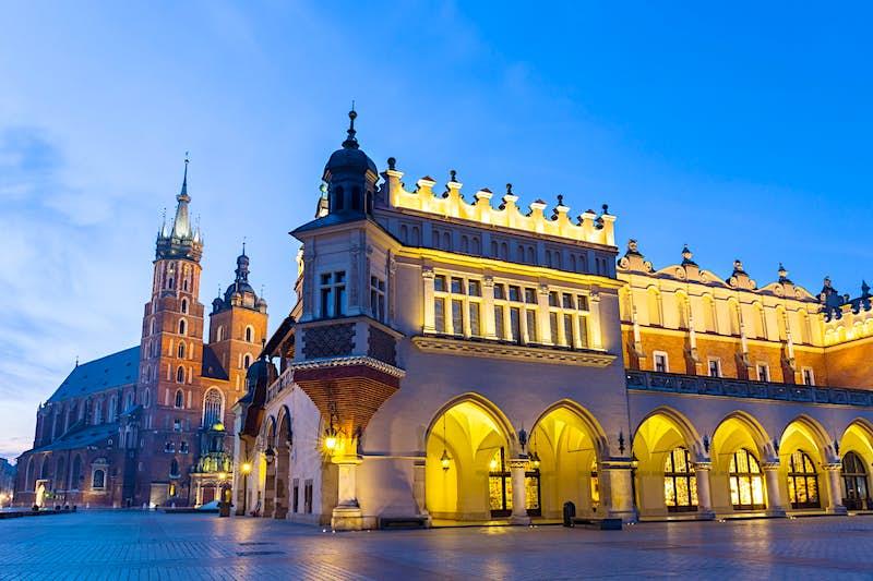 Illuminated Sukiennice building and St. Mary's Church at night, Krakow, Poland