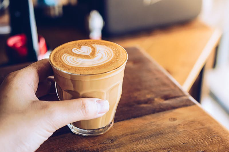 Travel News - Close-up of someone hand touching a shot glass of hot latte coffee in the cafe.