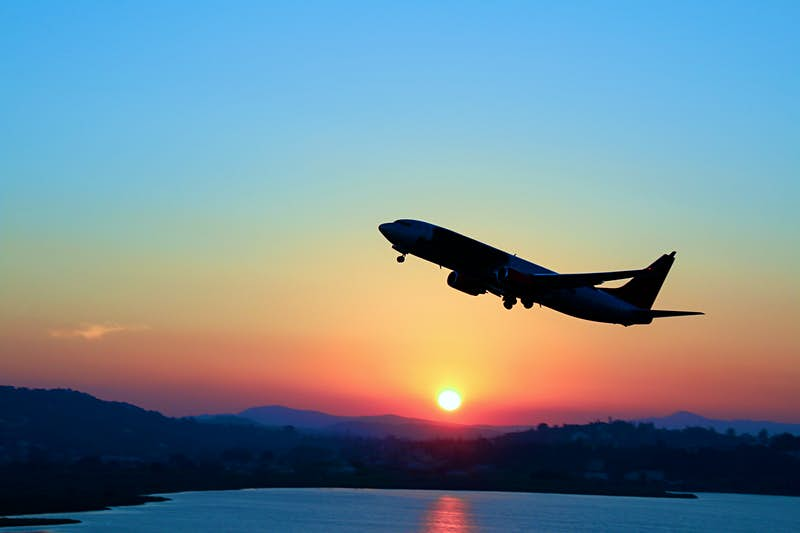 Travel News - Silhouette of an airplane just after take off during sunset