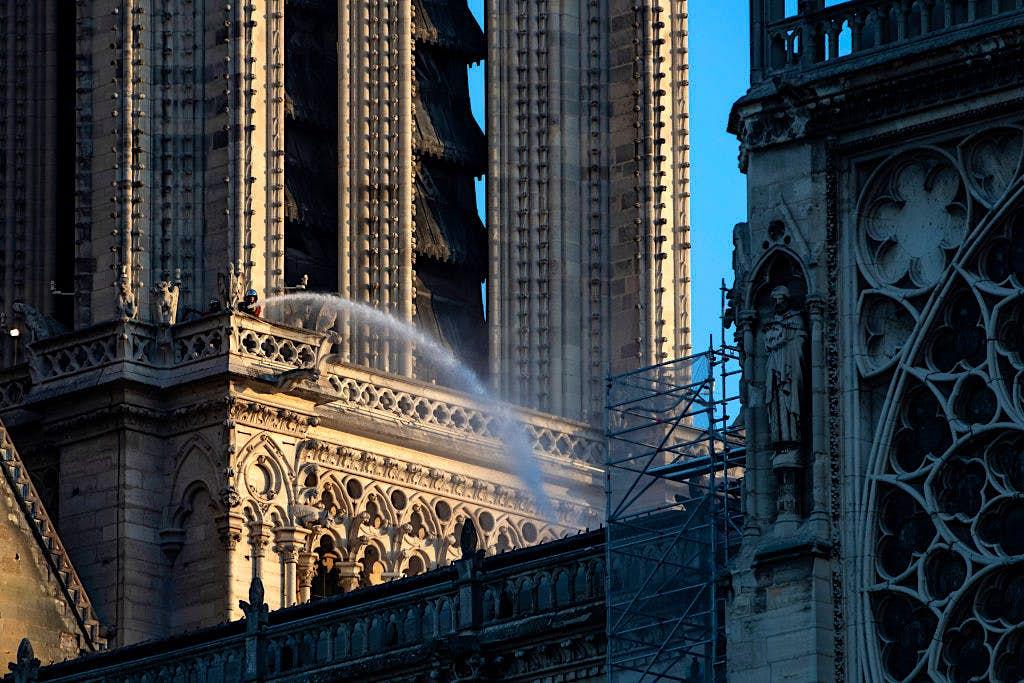 Un bombero baja una sección de la catedral de Notre Dame el día después del incendio masivo que devastó su techo