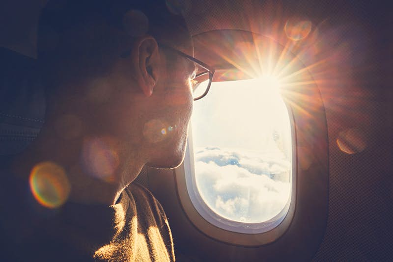 A man looks out the window of an airplane as the sun sets