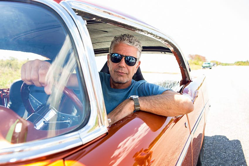 Anthony Bourdain driving a vintage car in Havana.