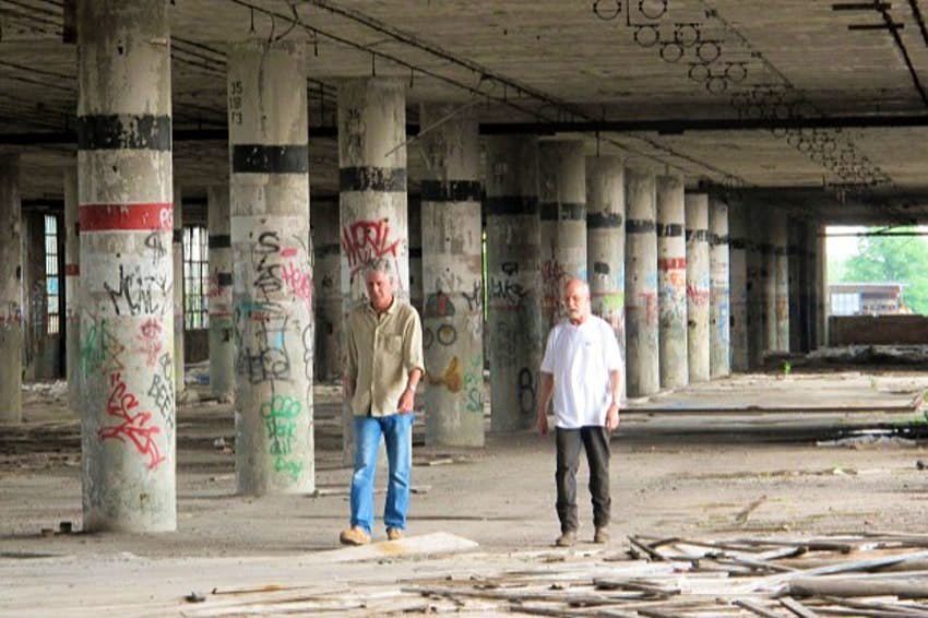 Anthony Bourdain walking through abandoned building with an another man in Detroit.