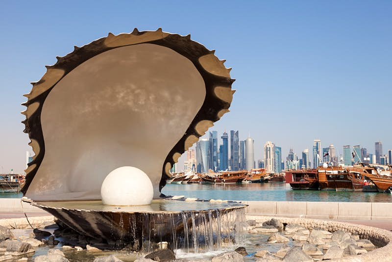 Fountain with cityscape of Doha in the background.