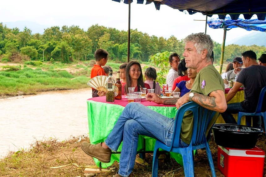 Anthony Bourdain sitting on the banks of a river in Korea.