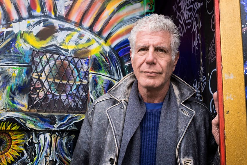 Anthony Bourdain at a decorated wall in the Lower East Side of New York CIty
