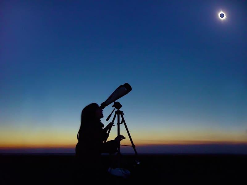 A woman watches a solar eclipse through a telescope