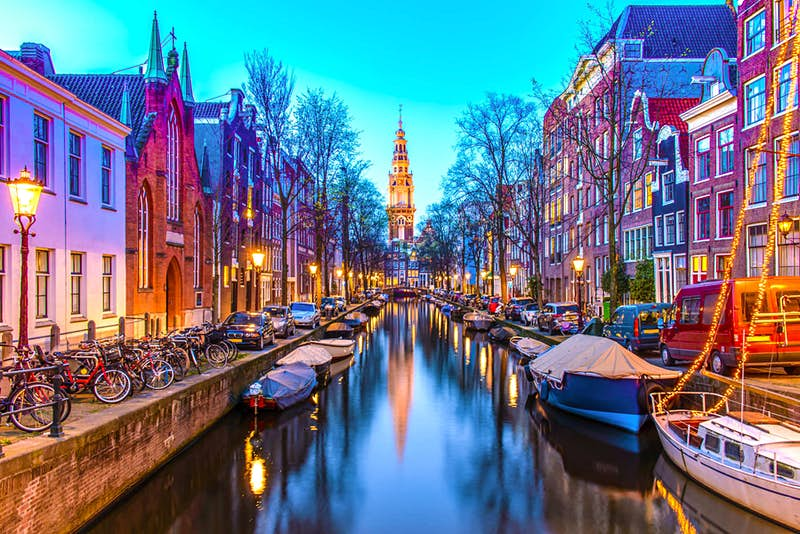 A view of a canal in Amsterdam by night.