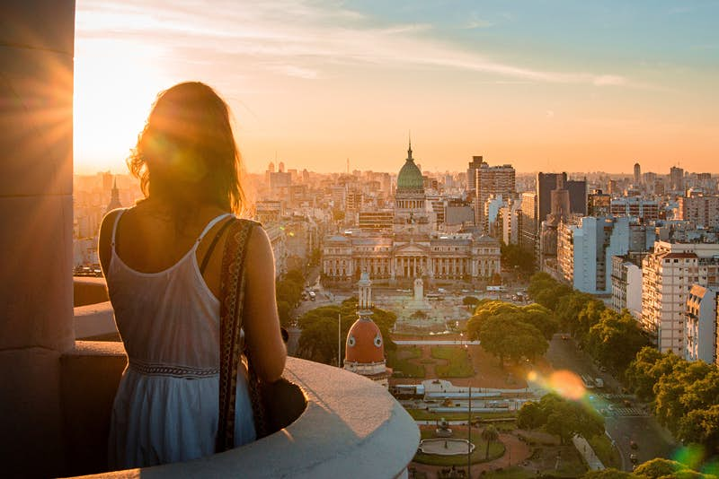 A woman standing on a balcony overlooking the Buenos Aires cityscape during sunset.