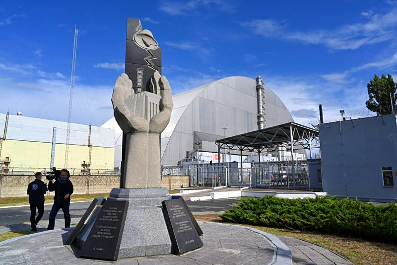 A monument near the New Safe Confinement metal dome encasing the destroyed reactor at Chernobyl.