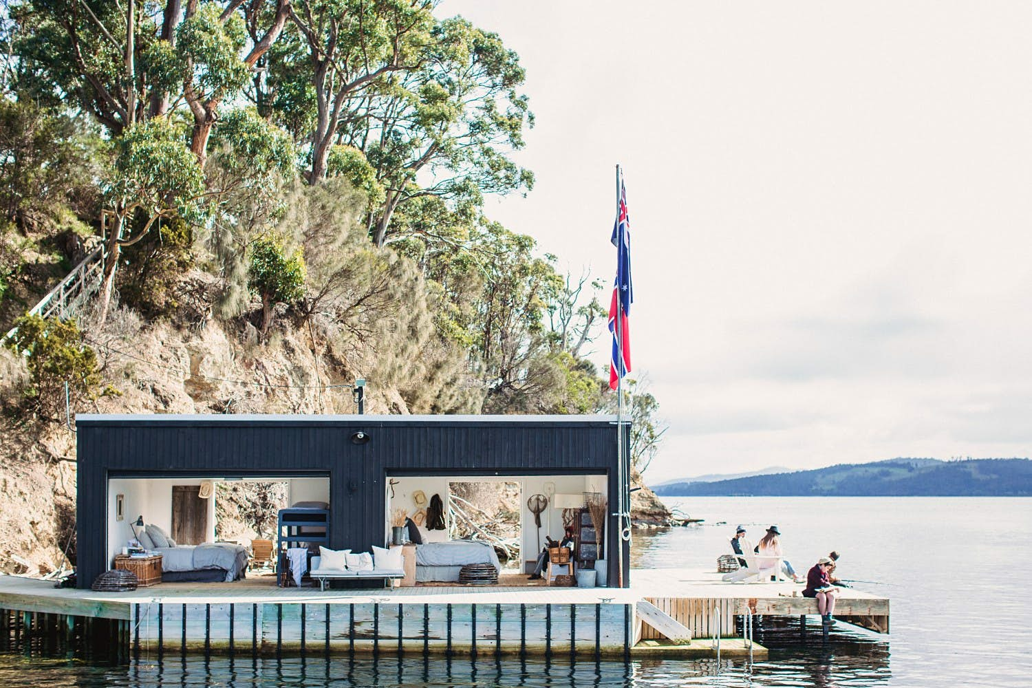People sitting outside the Boathouse on Satellite Island in Tasmania
