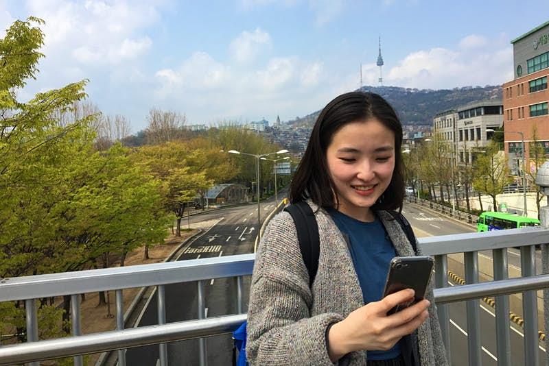 A girl looking at her phone in Korea