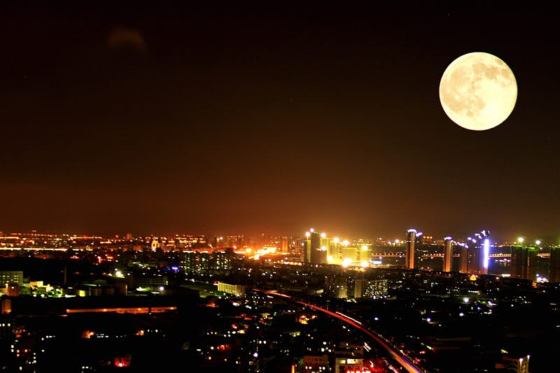 A supermoon over a city at night.