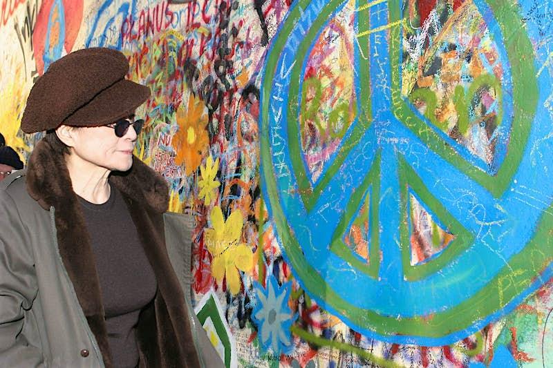 Yoko Ono looks at a peace symbol on the John Lennon Peace Wall in Prague.