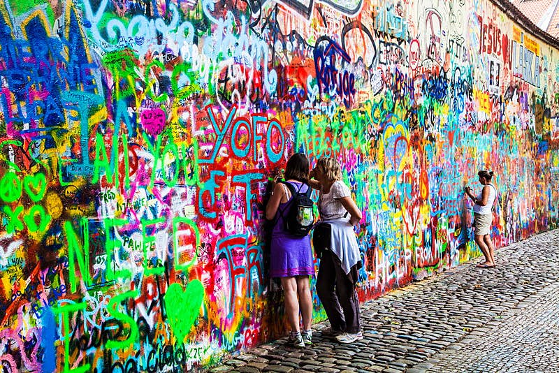 Two visitors add graffiti to the John Lennon Wall in Prague