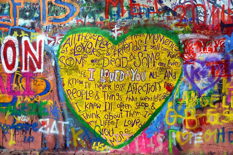 A big yellow heart painted by a tourist on the John Lennon Wall in Prague.